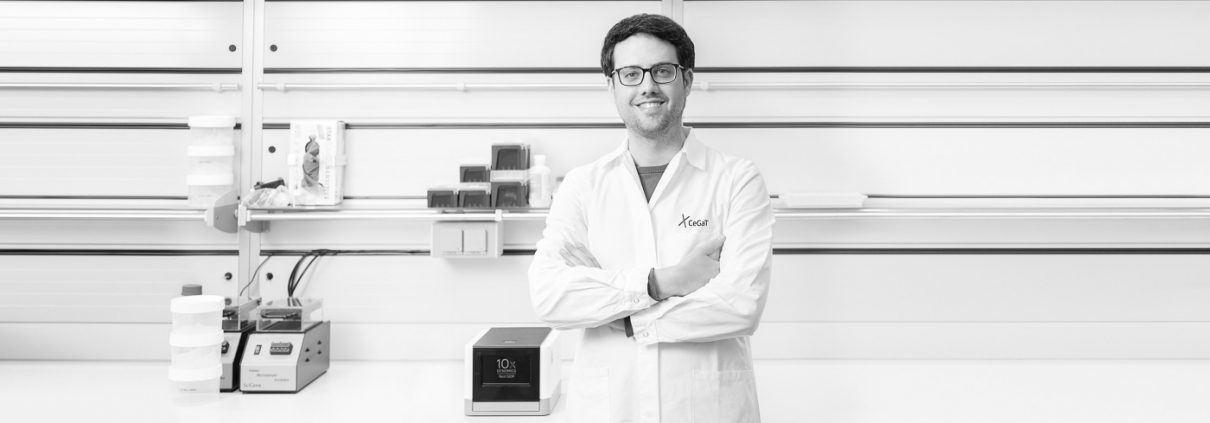 Young Scientist stands in front of 10X Genomics® Chromium™ system